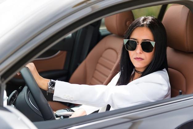 Belle jeune fille à l'intérieur d'une voiture de luxe