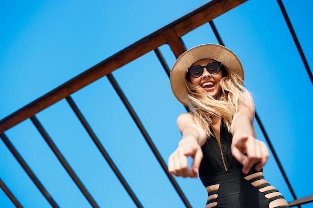 Belle jeune fille joyeuse en chapeau et lunettes de soleil se repose sur la plage du matin