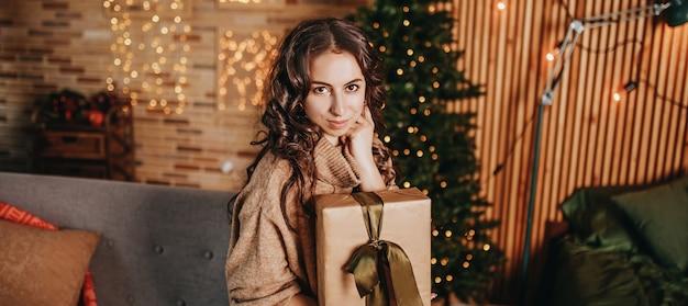 Belle jeune fille joyeuse et heureuse avec des cadeaux de noël sur un canapé sur fond d'arbre du nouvel an à la maison