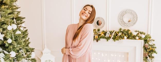 Belle jeune fille joyeuse et heureuse avec des cadeaux de noël sur le fond d'un arbre du nouvel an à la maison