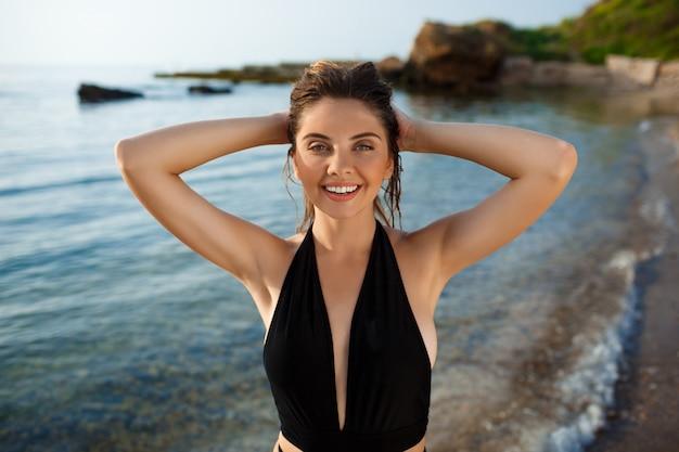 Belle jeune fille joyeuse reste sur la plage du matin