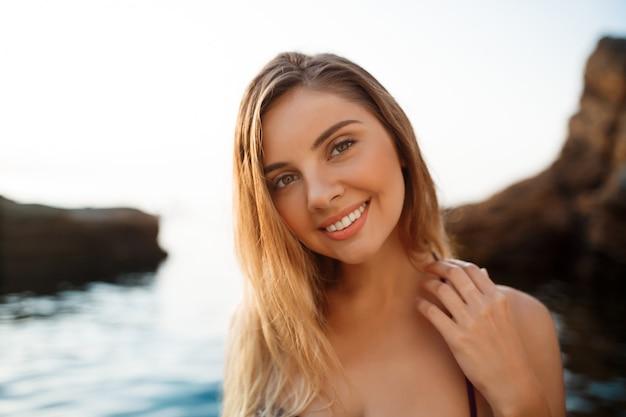 Belle jeune fille joyeuse se repose sur la plage du matin