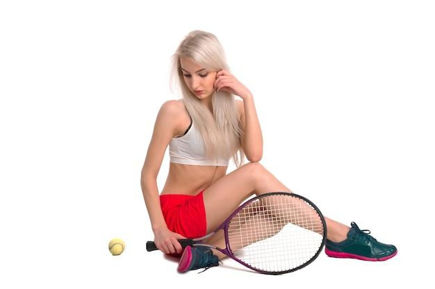 Belle jeune fille en jupe rouge assis sur fond blanc isolé avec une raquette de tennis et une balle