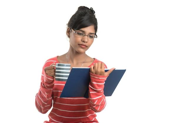 Belle jeune fille avec livre et tasse de café posant sur un mur blanc.