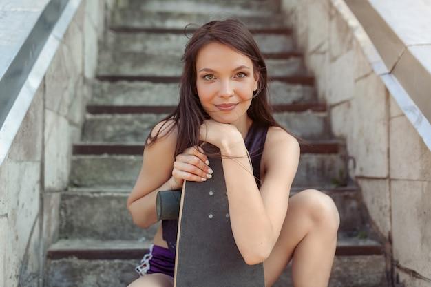 Belle jeune fille avec une longue planche dans la ville.