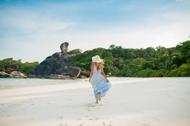 Belle jeune fille en longue robe bleue en cours d'exécution sur la plage