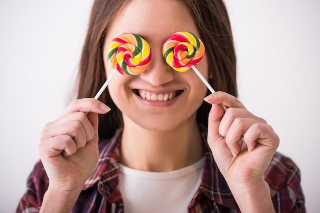 Belle jeune fille ludique avec deux sucettes colorées.