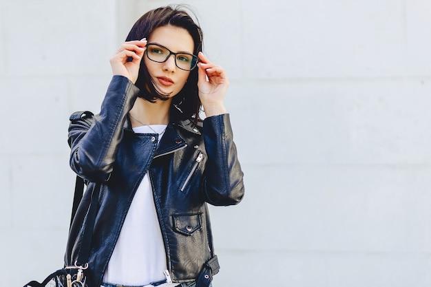 Belle jeune fille à lunettes dans des vêtements élégants sur fond clair