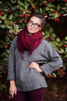 Belle jeune fille avec des lunettes et une écharpe bordeaux sur une surface d'un arbre avec des fruits rouges