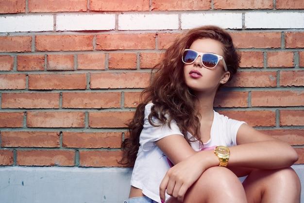 Belle jeune fille à lunettes de soleil sur fond de mur de briques. de beaux cheveux sains. short en jean