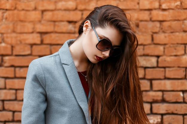 Belle jeune fille à lunettes de soleil et manteau gris regarde vers le bas près du mur de briques