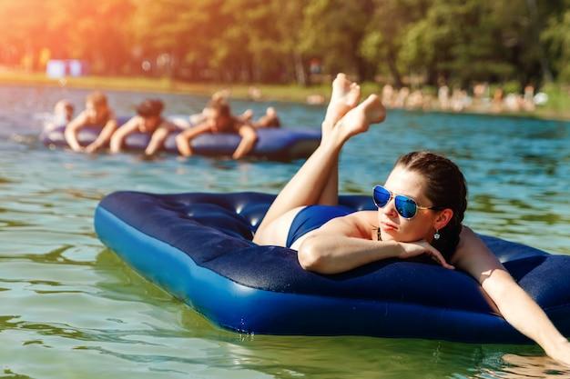 Une belle jeune fille en maillot de bain et lunettes de soleil est allongée sur un matelas à eau bleue contre la mer. le de vacances, vacances, été, vacances, voyages. fond