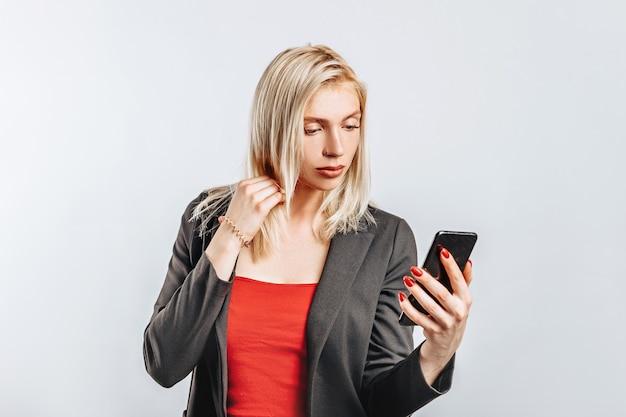 Belle jeune fille malheureuse et tenant le téléphone sur fond isolé gris