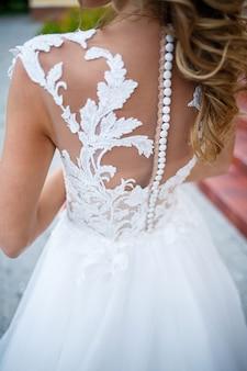 Belle jeune fille mariée en robe blanche avec un train marchant sur le fond d'une grande maison avec des colonnes le jour de leur mariage