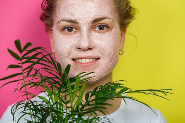 Belle jeune fille avec un masque rafraîchissant sur le visage. tenant une paume décorative dans ses mains. beauté et peau saine