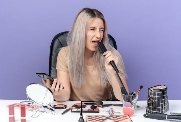 Une belle jeune fille mécontente est assise à table avec des outils de maquillage tenant un peigne avec un téléphone isolé sur fond bleu