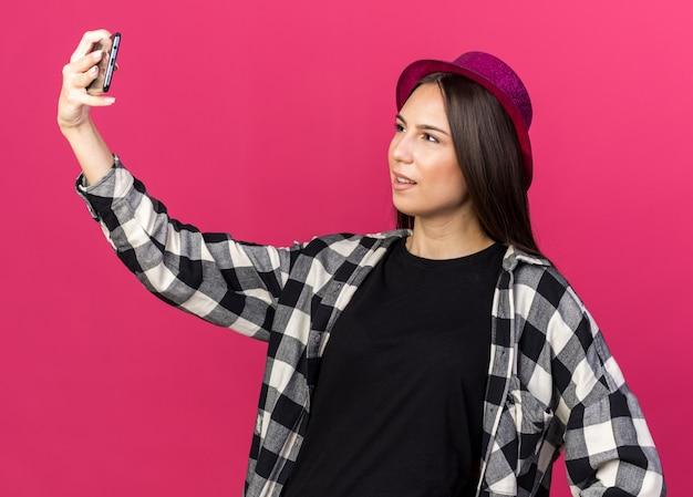 Une belle jeune fille mécontente portant un chapeau de fête prend un selfie