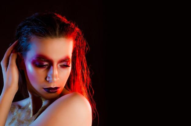 Belle jeune fille à la mode avec le maquillage d'art en lumière de couleur
