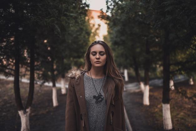 Belle jeune fille modèle blonde. pantalon blanc. pull tricoté gris. bottes noires. . pendentif en bois sur le cou en forme de cheval. dans un manteau brun posant. sur le coucher du soleil. portrait. près des arbres