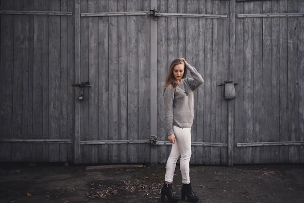 Belle jeune fille modèle blonde. pantalon blanc. pull tricoté gris. bottes noires. pendentif en bois sur le cou en forme de cheval.