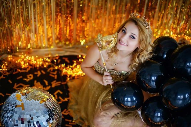 Belle jeune fille modèle blonde souriante couvre son visage avec un masque de carnaval dans une élégante robe en or avec un fond de cornes de cerceau de rubans de lotus avec des guirlandes assis sur le sol.