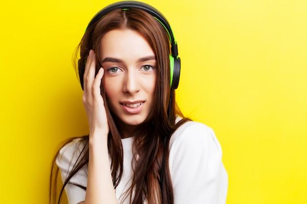 Belle jeune fille modèle écoute de la musique dans les écouteurs sur jaune