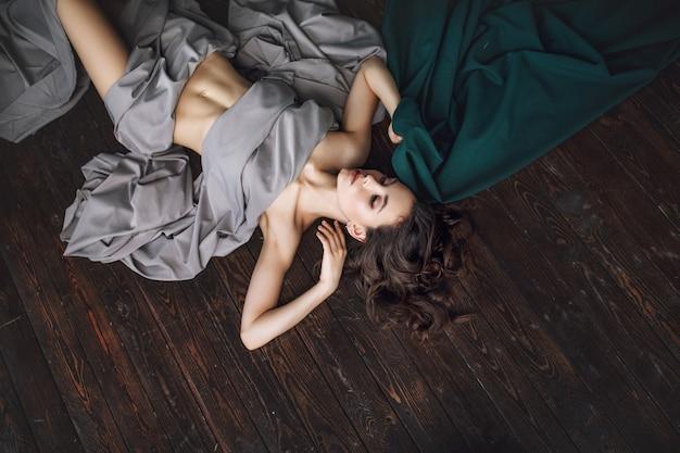 Belle jeune fille modèle avec maquillage et coiffure en tissu fluide couché sur la vue de dessus de plancher en bois