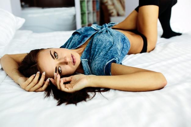 La belle jeune fille à moitié vêtue se trouve sur un lit blanc