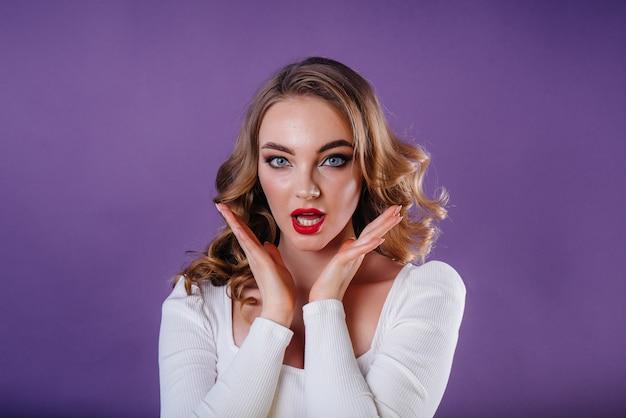 Une belle jeune fille montre des émotions et des sourires dans le studio sur un espace violet. les filles pour la publicité.