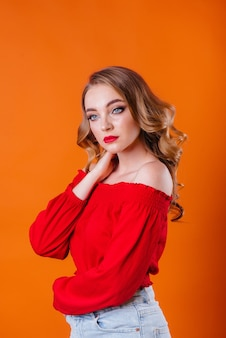 Une belle jeune fille montre des émotions et des sourires dans le studio sur un fond orange. filles pour la publicité.