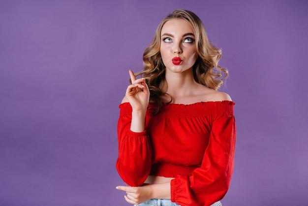 Une belle jeune fille montre des émotions et des sourires dans le studio sur un fond violet. filles pour la publicité.