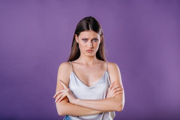 Une belle jeune fille montre des émotions et des sourires sur un espace violet. les filles pour la publicité.