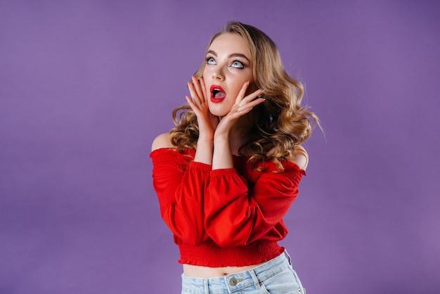 Une belle jeune fille montre des émotions et des sourires sur un espace violet.