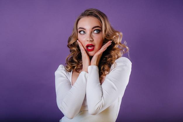 Une belle jeune fille montre des émotions et des sourires en studio sur fond violet. les filles pour la publicité.