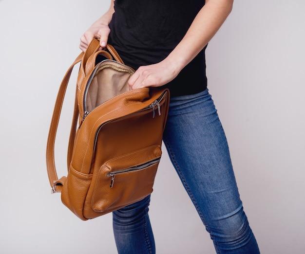 Une belle jeune fille montre un sac à dos en cuir marron dans la publicité d'accessoires en cuir de studio