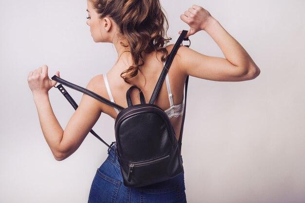 Une belle jeune fille montre un sac à dos en cuir marron dans le studio. publicité d'accessoires en cuir. bagage à main. grand sac à dos fait main spacieux