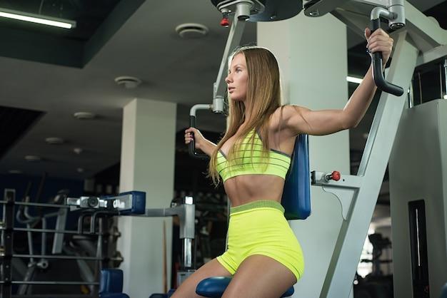 Belle jeune fille musculaire athlétique sexy. fille de remise en forme caucasienne s'entraîne dans le gymnase