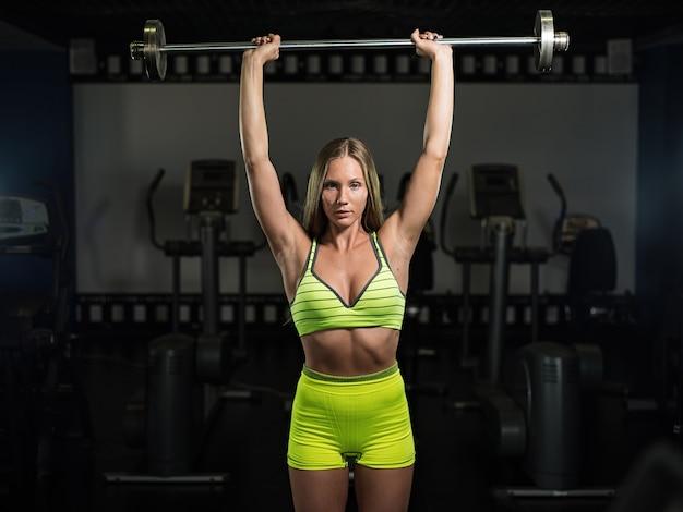 Belle jeune fille musculaire athlétique sexy. fitness fille s'entraîne dans le gymnase, faisant des exercices avec une barre
