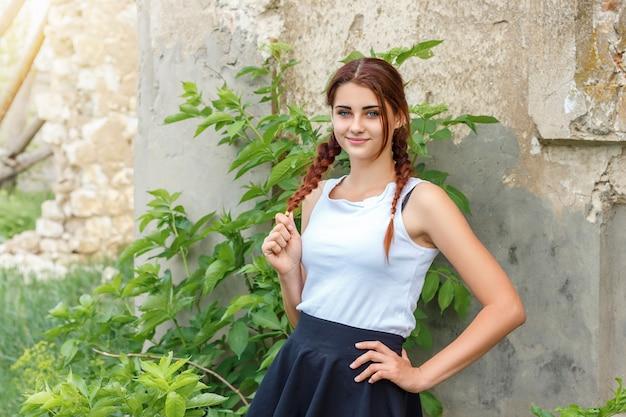 Belle jeune fille avec des nattes debout près d'un mur de briques.
