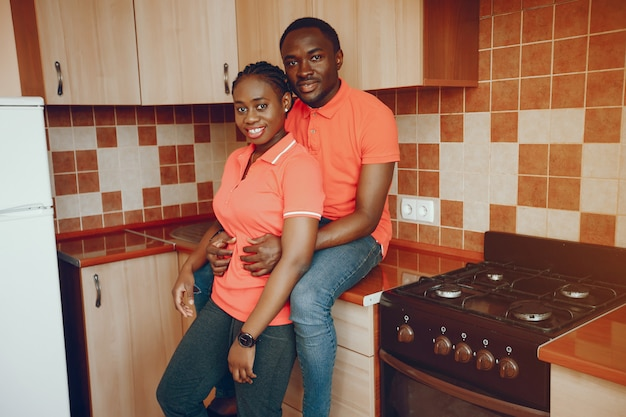 Une belle jeune fille noire dans un t-shirt rose et un jean bleu debout à la maison dans la cuisine