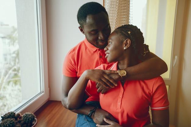 Une belle jeune fille noire dans un t-shirt rose et un jean bleu debout à la maison près de la fenêtre