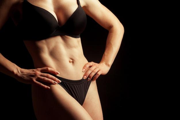 Belle jeune fille nue isolée sur un fond noir