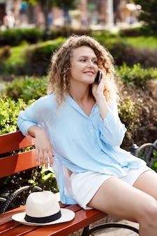 Belle jeune fille parlant au téléphone, assis au banc.