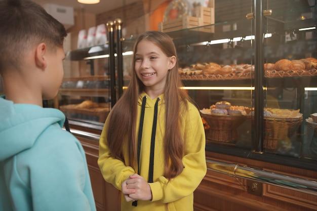 Belle jeune fille parlant à son frère à la boulangerie locale