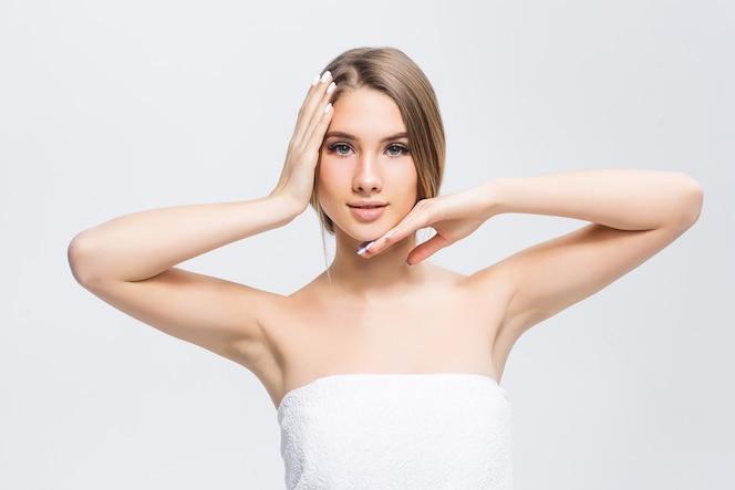 Belle jeune fille à la peau lisse sur un mur clair avec du maquillage naturel
