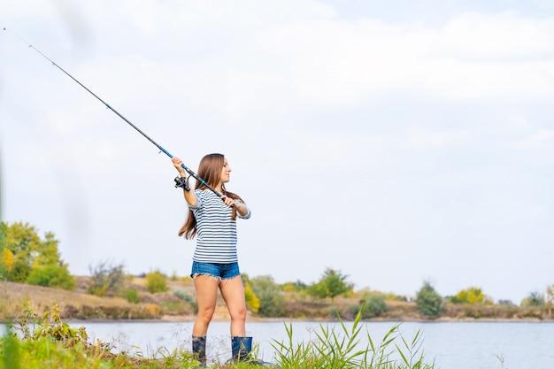 Belle jeune fille pêche sur le lac.