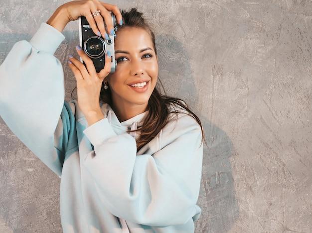 Belle jeune fille photographe souriante, prendre des photos à l'aide de son appareil photo rétro.