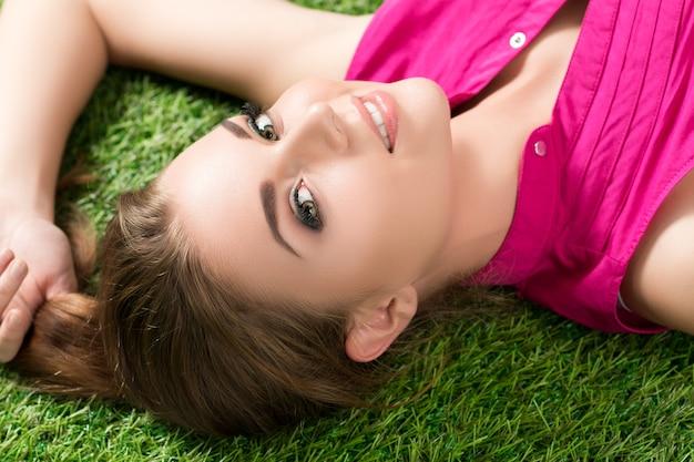 Belle jeune fille portant sur l'herbe dans le parc
