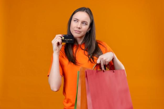Belle jeune fille portant un t-shirt orange tenant un paquet de papier et une carte de crédit à côté sournoisement debout sur fond orange isolé