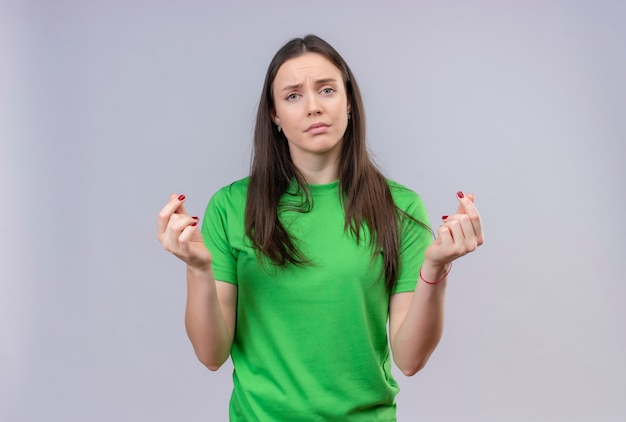 Belle jeune fille portant un t-shirt vert regardant la caméra mécontent de se frotter les doigts faisant un geste en espèces demandant de l'argent debout sur fond blanc isolé